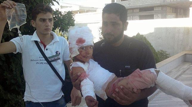 Una niña herida es sacada del hospital por dos parientes cerca de Homs, en julio de 2012