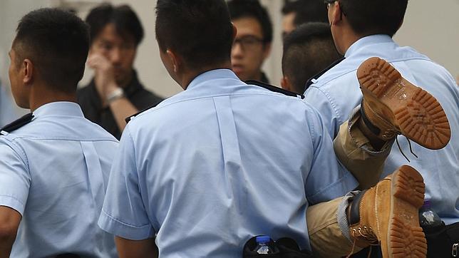 Agentes de la Policía trasladan a un detenido durante las multitudinarias protestas en Hong Kong
