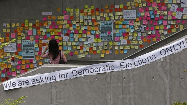 Una mujer mira los carteles prodemocracia en Hong Kong