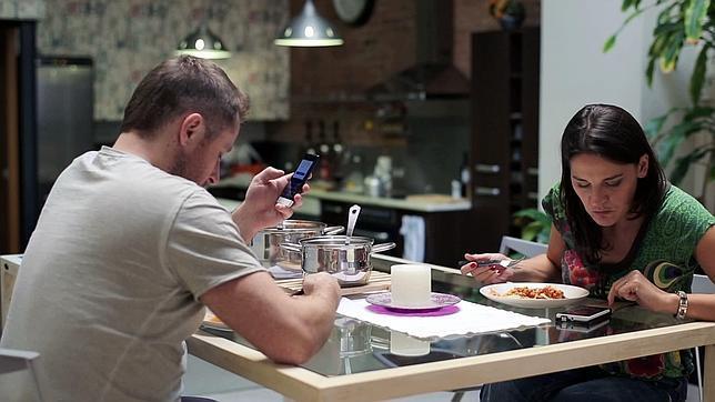 Dos personas revisan sus teléfonos mientras comen