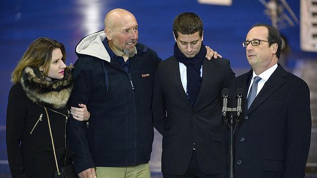 Serge Lazarevic (c) junto a sus hijos y el presidente francés a su llegada a París