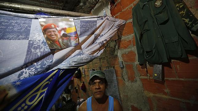 Un vecino de un barrio marginal de Caracas exhibe un cartel de Chávez