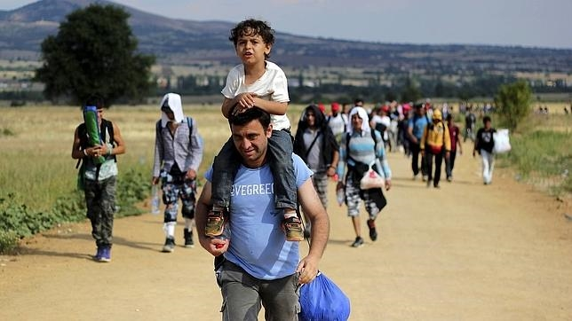 Un inmigrante lleva a hombros a un niño mientras camina hacia Presevo, en Serbia
