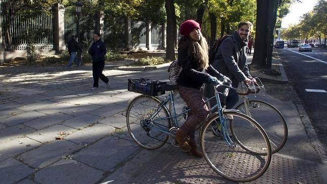 Dos madrileños circulan en bici por el Paseo del Prado