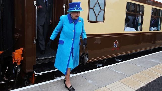 Isabel II con todas las prendas de esta temporada: atuendo monocolor, bolso de mano de los años 50, tacón grueso, guantes y broche