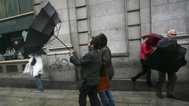 Los madrileños luchan contra el viento y la lluvia en la Gran Vía