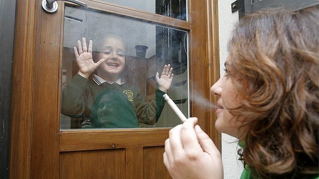 Una madre fuma en el patio de su casa para no perjudicar a su hija