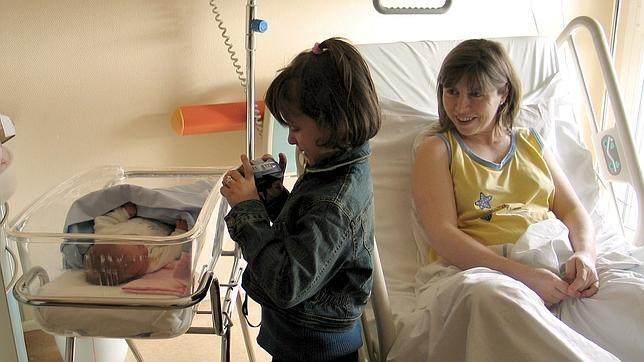 Imagen de archivo en la que aparece un bebé junto a su madre y su hermana en un hospital