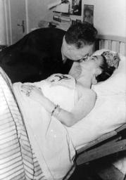 Diego besa a Frida, ingresada en el hospital (Ciudad de México, 1950). Ella, engalanada profusamente, luce en su pecho la hoz y el martillo. John Woodmann