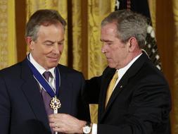 Momento en el que George W. Bush  impone la condecoración al ex primer ministro británico Tony Blair durante la ceremonia que se ha celebrado en la Casa Blanca. /Reuters