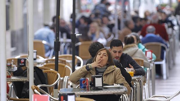 Una mujer fuma un cigarrillo en una terraza de la calle de la Plata