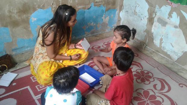 Una profesora y sus alumnos juegan a retos matemáticos en un centro preescolar de Dheli, en la India