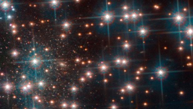 La imagen del Hubble muestra una parte del cúmulo globular NGC 6752. Detrás de las brillantes estrellas del cúmulo, se ve una colección más densa de estrellas débiles estrellas, una galaxia esferoidal enana desconocida hasta ahora