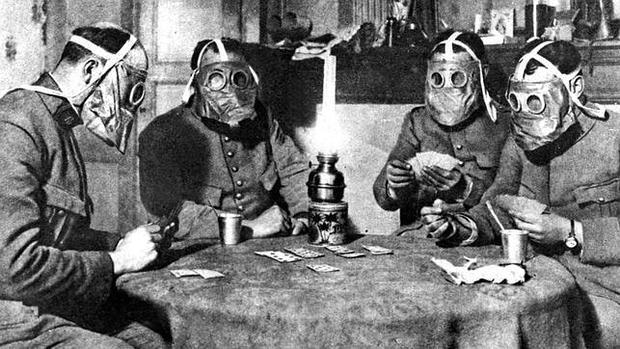Varios soldados juegan a las cartas protegidos con rudimentarias máscaras de gas