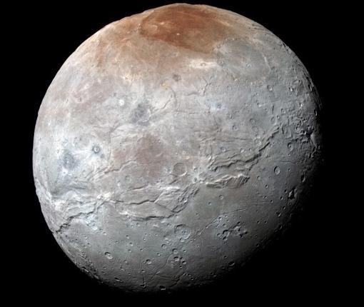 Vista en color mejorada de la luna más grande de Plutón, Caronte. Los colores están procesados para resaltar la variación de las propiedades de la superficie en la luna; lo más llamativo es la región polar norte (superior) rojiza.