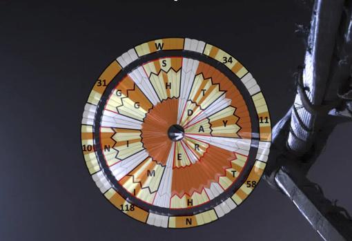 Esta ilustración muestra el diagrama superpuesto sobre el paracaídas desplegado durante el descenso del rover Mars Perseverance. El ingeniero de sistemas Ian Clark usó un código binario para deletrear «Dare Mighty Things» y las coordenadas GPS del JPL en Pasadena en las tiras naranjas y blancas del paracaídas, de 21 metros de diámetro