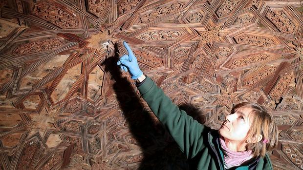 Una restauradora señala las piezas de madera que conforma la cúpula del templete oeste del Patio de los Leones