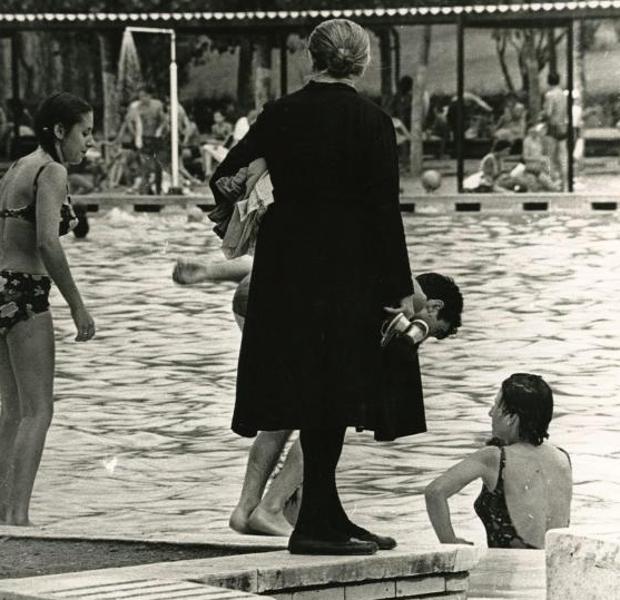Una mujer vestida de negro en una piscina pública en el año 1968