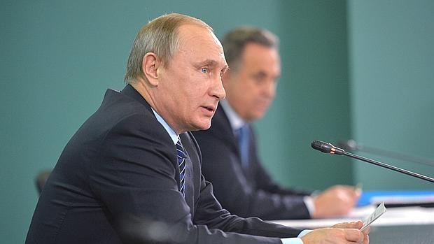 El presidente ruso Vladimir Putin, con su ministro de Deportes al fondo