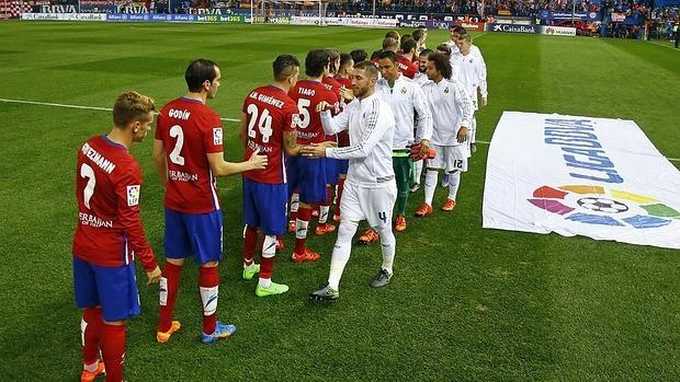 Los jugadores se saludan en el derbi del Calderón