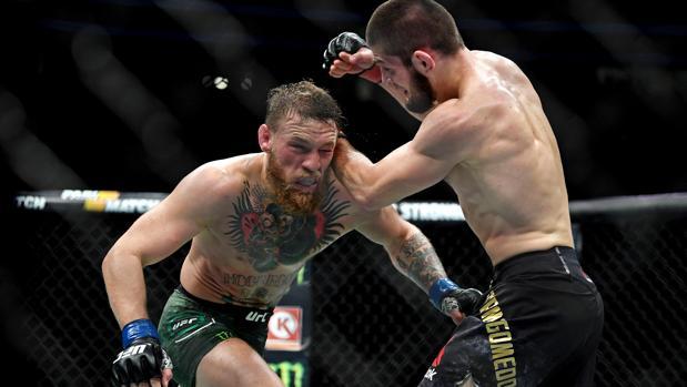 Conor McGregor (i) intercambia golpes con Khabib Nurmagomedov (d)