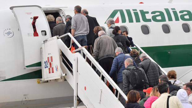 Un grupo de pasajeros subiendo a un avión de Alitalia