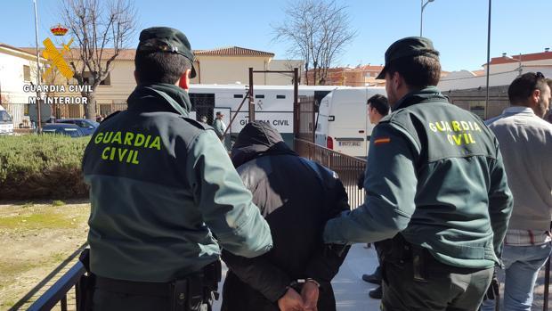 Uno de los detenidos, camino del furgón de la Guardia Civil para su traslado