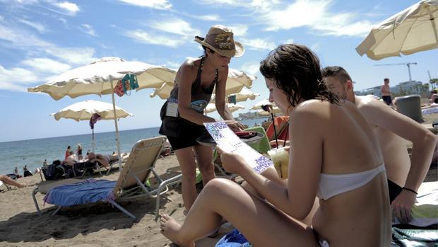 Una camarera de un chiringuito de la Barceloneta atiende a dos personas en 2012