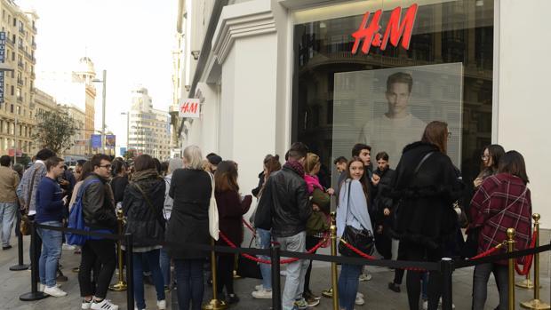 Decenas de personas hacen cola en la tienda de H&M en la Gran Vía, 37