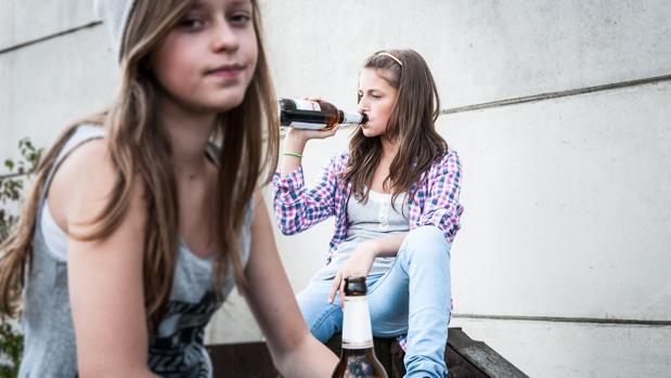 Dos jóvenes bebiendo cerveza en la calle