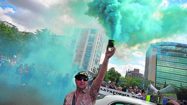 Un taxista levanta un tubo de humo durante la manifestación de este miércoles en Madrid