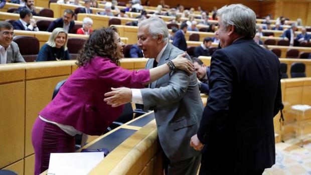 La ministra de Hacienda, María Jesús Montero saluda al vicesecretario de Política Autonómica y Local del PP, Javier Arenas, hoy en el Senado