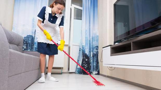 Una camarera de piso limpiando en una habitación de hotel