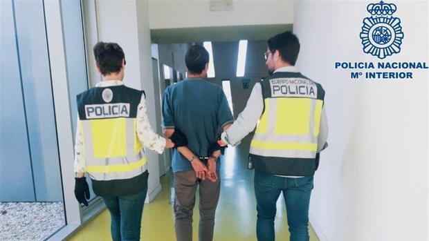 Dos agentes de la Policía Nacional llevan esposado al detenido
