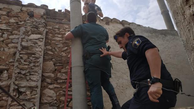 Dos guardias civiles y un policía local en el momento de sacar al bebé de la vivienda incendiada