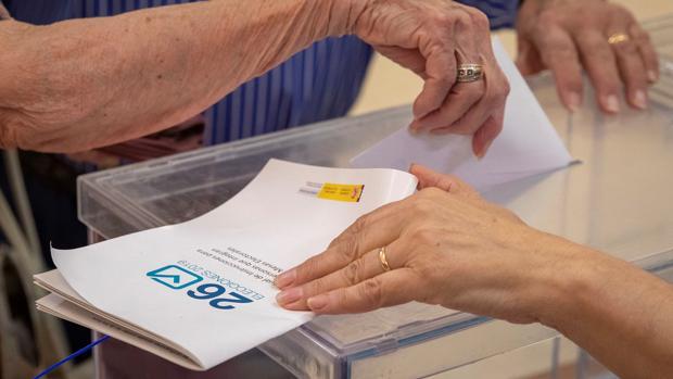 Una ciudadana deposita su voto en la urna este mediodía