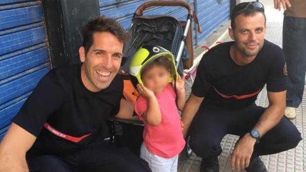 La pequeña, con su casco, con los bomberos que la rescataron
