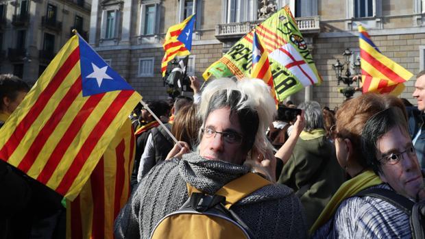 Una mujer con una careta de Carles Puigdemont ante el Palau de la Generalitat
