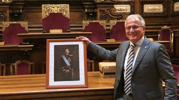 Imagen del presidente del Grupo Municipal del PP en Barcelona, Josep Bou, agarrando el retrato del Rey Don Felipe
