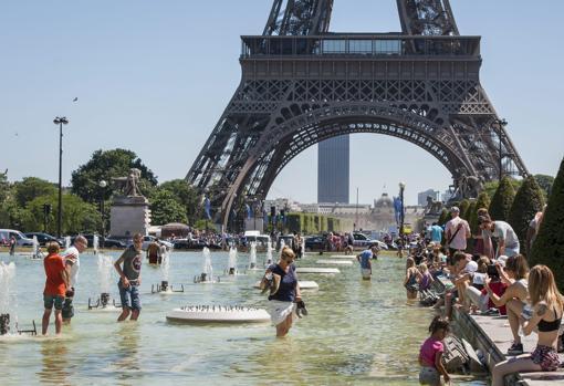 Imagen de archivo de una multitud de turistas refrescándose en la fuente de los jardines del Trocadero