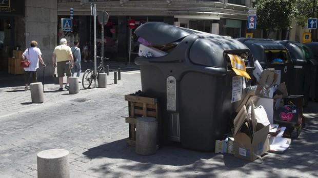 Un contenedor de carton, a rebosar, en la plaza de Santa Ana a mediodía