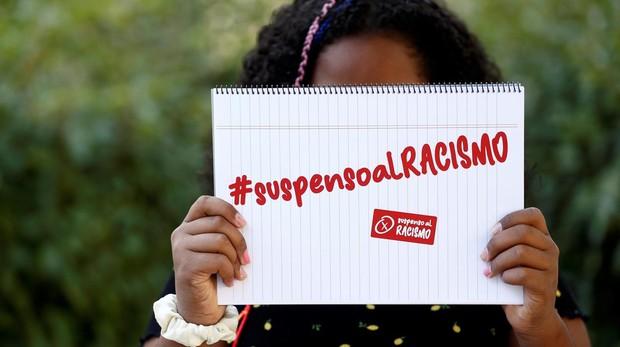 La menor posa con el lema que han lanzado sus padres contra el racismo