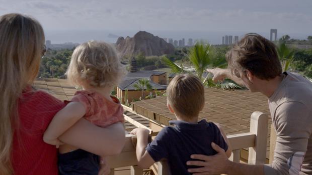 Una familia disfruta de las vistas a las zonas de animales en libertad desde una cabaña del resort