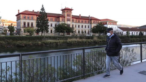 Una persona pasea por el margen del río Urumea, frente al acuartelamiento de Loyola