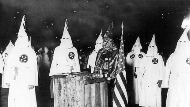 Miembros del Klan, junto a la bandera norteamericana
