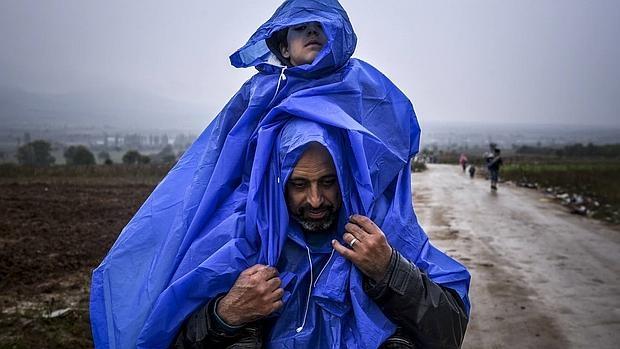 Un refugiado cruza la frontera entre Macedonia y Serbia con su hijo a hombros