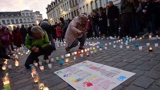 Un grupo de manifestantes del distrito de Molenbeek ponen velas en homenaje a las víctimas de París