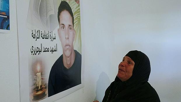 La madre de Bouazizi ante un retrato del joven, que se inmoló hace cinco años