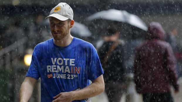 Un hombre partidario de la permanencia del Reino Unido en la UE camina este jueves, jornada electoral lluviosa, por el centro de Londres