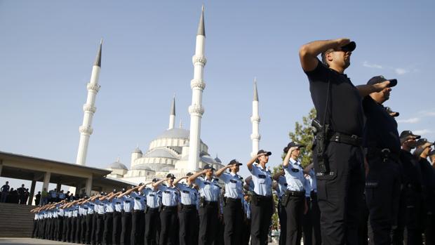 Varios agentes de policía se unen para rendir tributo a los policías caídos en el intento de golpe ayer, en la Mezquita Kocatepe en Ankara, REUTERS